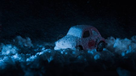 close-up shot of toy car covered with snow in night