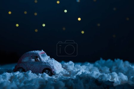 close-up shot of toy car standing in snow in night under starry sky, christmas concept