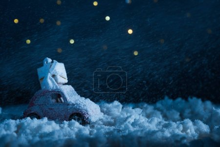 Photo for Close-up shot of toy car with gift box standing in snow in night under starry sky, christmas concept - Royalty Free Image