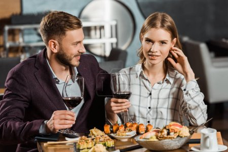 Beautiful young adult couple drinking wine and eating sushi in restaurant