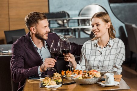 Beautiful couple clinking while having dinner in restaurant