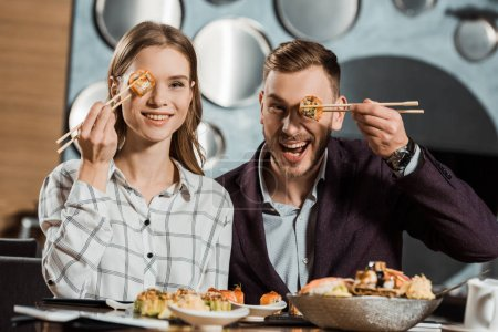 Lovely couple having fun while eating sushi rolls in restaurant