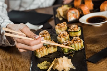 Partial view of woman eating sushi rolls with chopsticks