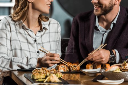 Partial view of smiling couple eating sushi in restaurant