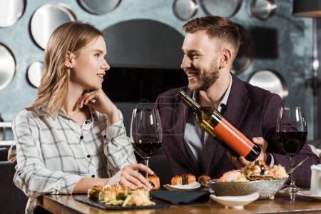 Photo pour Beau homme offrant à sa petite amie du vin pendant qu'ils dînent au restaurant - image libre de droit