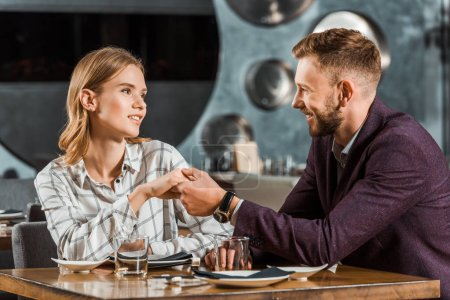 Attractive young adult couple holding hands while sitting in restaurant