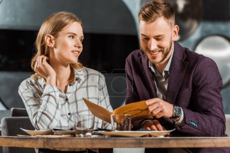 Happy smiling couple looking in menu to order dinner in restaurant