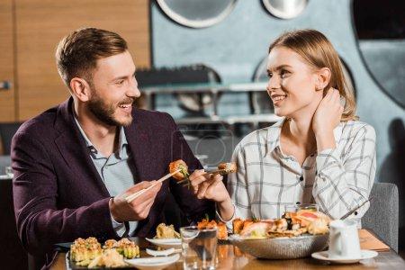 Attractive smiling couple having dinner in restaurant