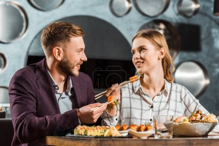 Happy young adult couple looking at each other while having dinner together in restaurant