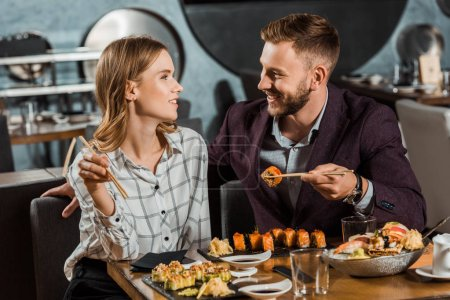 Happy young adult couple looking at each other while eating sushi rolls in restaurant