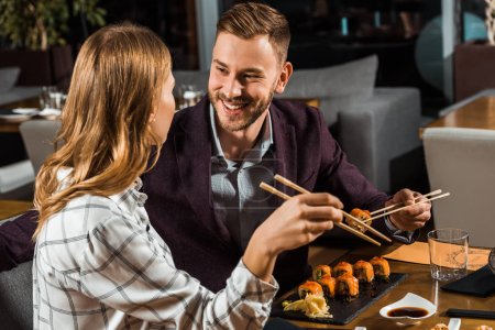 Beautiful happy couple eating sushi rolls in restaurant
