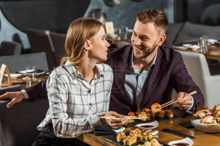 Attractive smiling couple amorously looking at each other while having dinner in restaurant
