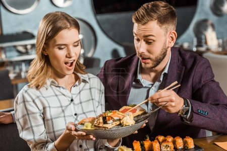 Surprised woman holding plate with seafood while couple having dinner in restaurant