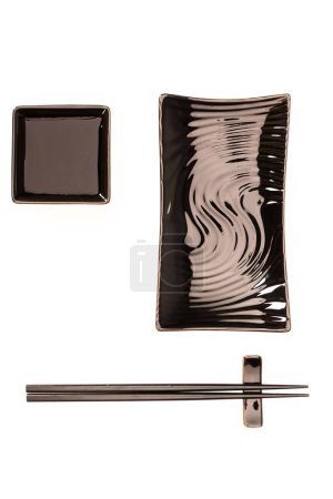 Photo pour Vue de dessus des plaques noires pour les rouleaux de sushi et de sauce de soja avec des baguettes isolé sur blanc - image libre de droit