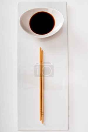 Photo for Top view of plate with soy sauce and chopsticks on white slate - Royalty Free Image