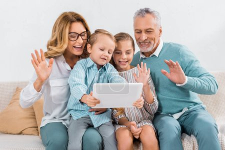 grandchildren and grandparents waving by hands while having video call with digital tablet at home