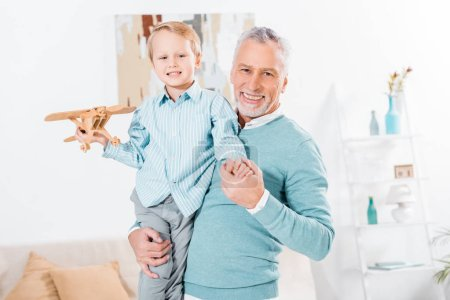 happy middle aged man holding little grandson with wooden airplane on hands at home
