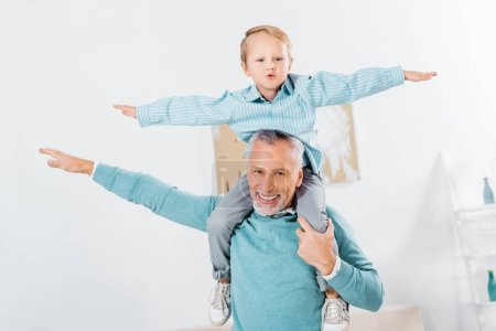 Photo for Child sitting on happy grandfather shoulders and imitating plane at home - Royalty Free Image