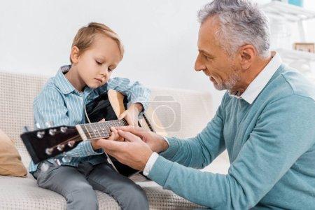 Photo pour Vue latérale d'un homme d'âge moyen enseignant le petit-fils à jouer de la guitare acoustique à la maison - image libre de droit
