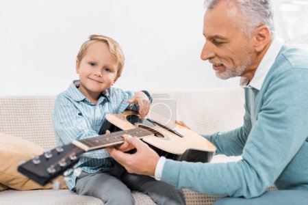 selective focus of middle aged man teaching grandson playing on acoustic guitar at home