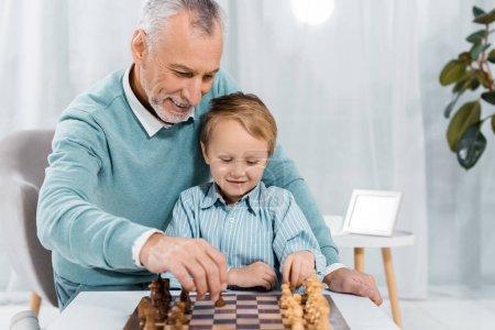 Photo pour Souriant homme d'âge moyen enseignant petit-fils à jouer aux échecs à la maison - image libre de droit