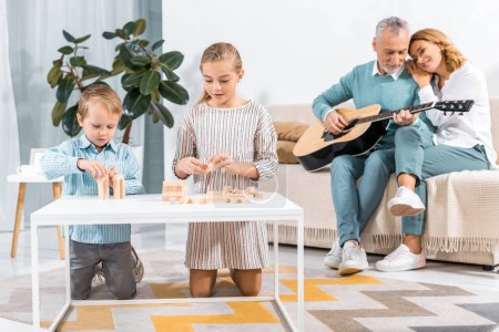 selective focus of children playing blocks wood game tower while their grandparents playing on guitar behind at home