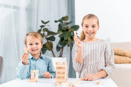 selective focus of happy adorable children playing blocks wood tower game at home