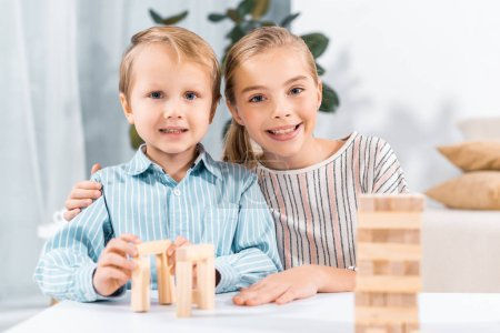 portrait of smiling child embracing little brother at table with blocks wood tower game at home