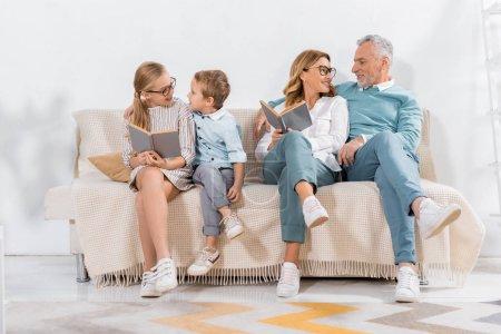 happy grandchildren and grandparents reading books on sofa at home