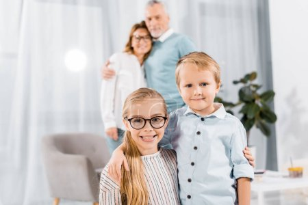 portrait of happy brother and sister embracing while their grandparents standing behind at home
