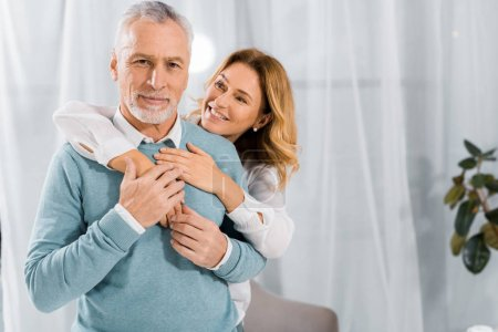 happy wife embracing mature husband from behind at home