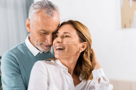 close up view of handsome middle aged man embracing laughing woman at home