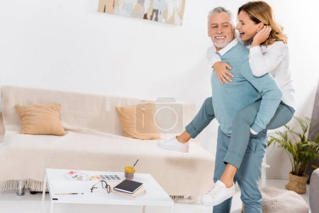 Photo for Happy middle aged man doing piggyback ride to beautiful wife in living room at home - Royalty Free Image