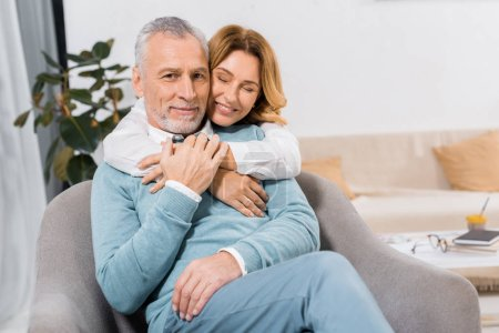 attractive woman with closed eyes embracing middle aged husband at home