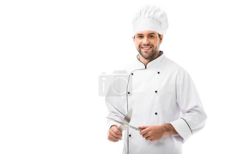 Photo for Handsome young chef holding cutting knives and looking at camera isolated on white - Royalty Free Image