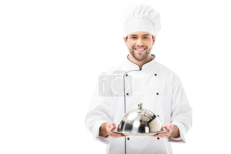 smiling young chef holding serving tray with dome and looking at camera isolated on white