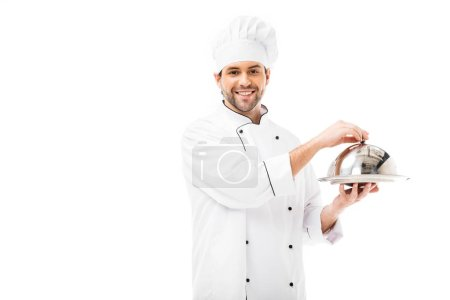 handsome young chef holding serving dish with dome and looking at camera isolated on white
