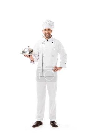Photo pour Jeune chef souriant tenant assiette de service avec dôme et regardant la caméra isolée sur blanc - image libre de droit