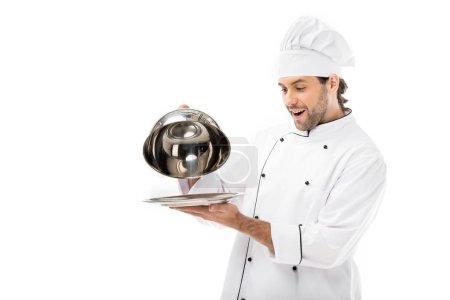 Photo pour Surpris jeune chef prise de servir dôme de plaque isolée sur blanc - image libre de droit