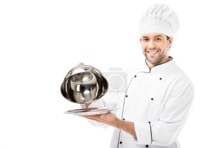 smiling chef taking of serving dome from plate isolated on white