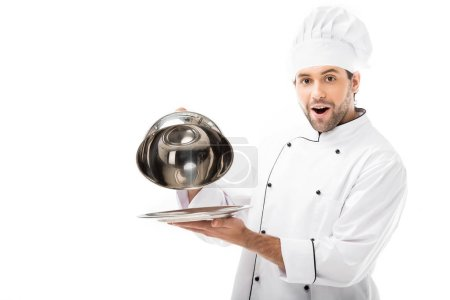 excited young chef taking of serving dome from plate and looking at camera isolated on white