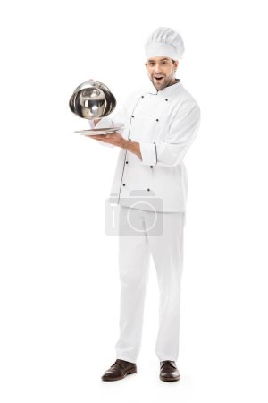 emotional young chef taking of serving dome from plate isolated on white