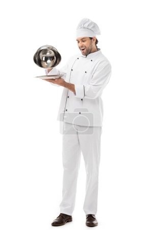 expressed young chef taking of serving dome from plate isolated on white