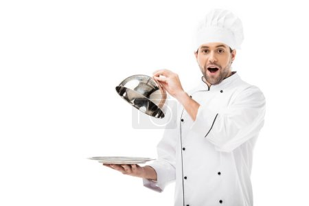 surprised young chef taking of serving dome from plate and looking at camera isolated on white