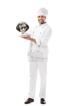 happy young chef taking of serving dome from plate and looking at camera isolated on white