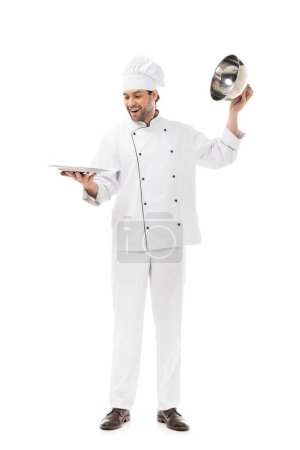 happy young chef taking of serving dome from plate isolated on white