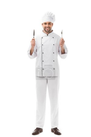 smiling young chef holding knife and fork and looking at camera isolated on white