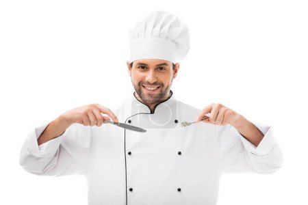 Photo for Happy young chef holding fork and knife and looking at camera isolated on white - Royalty Free Image