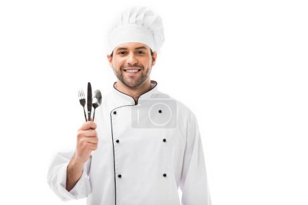 smiling young chef holding bunch of cutlery isolated on white