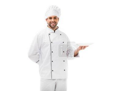Photo pour Beau jeune chef tenant la plaque vide et regardant la caméra isolée sur blanc - image libre de droit